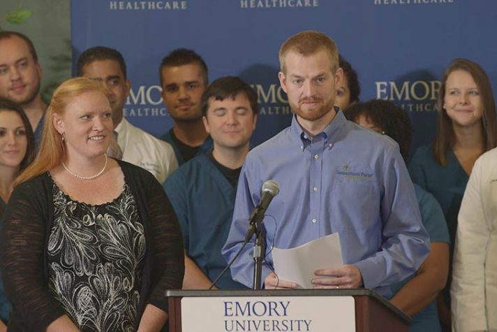 Kent Brantly and wife, Amber, stand at podium, doctors and nurses behind them