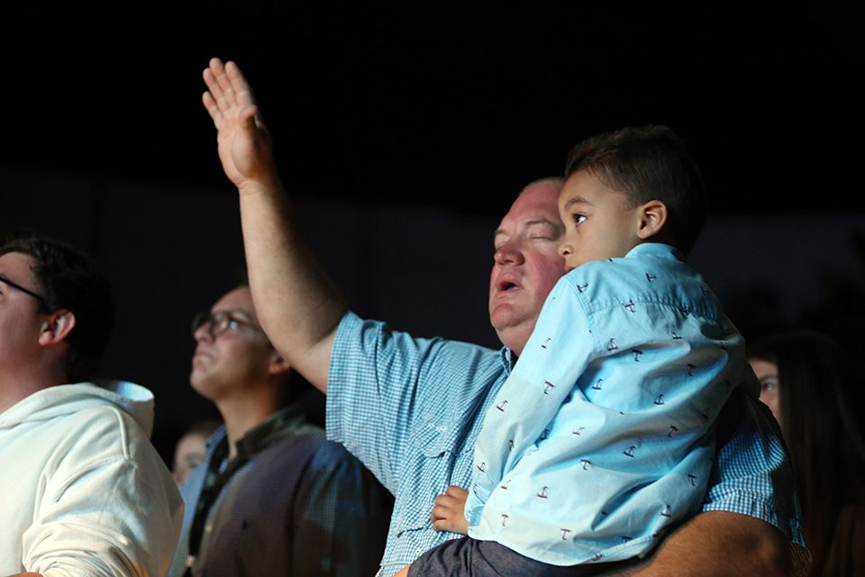 Man with arm raised in worship, holding little boy