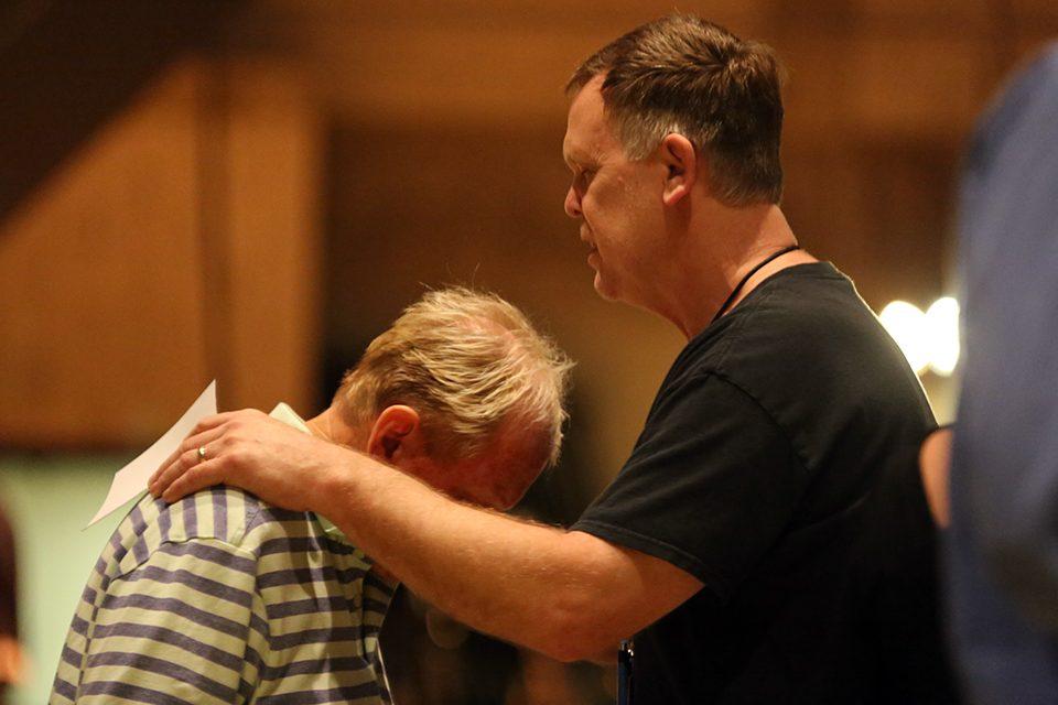 Man praying with another man who received Christ