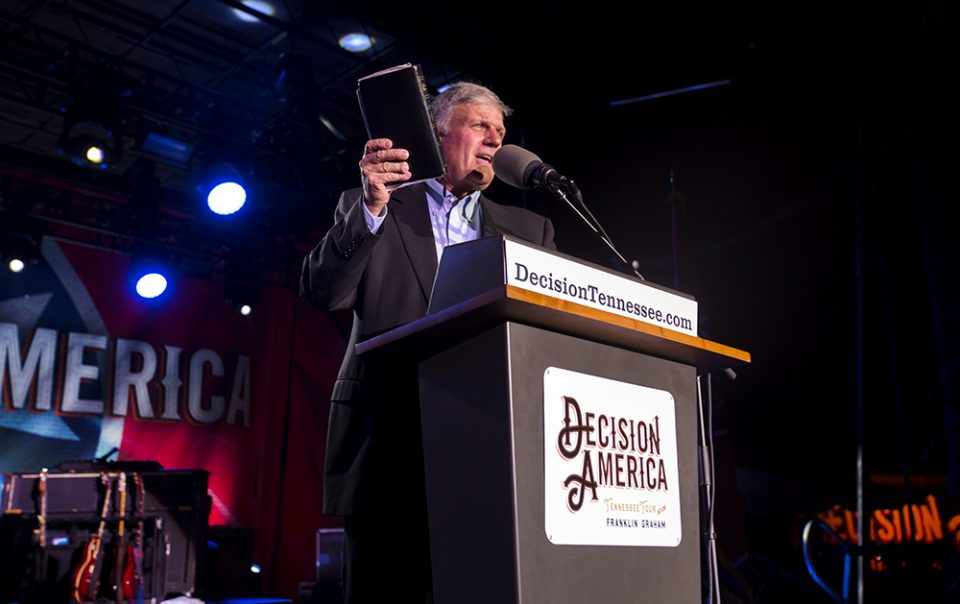 Franklin Graham at podium, holding Bible