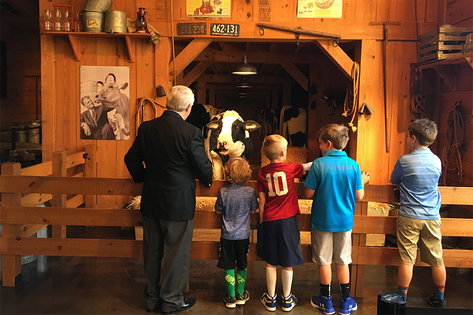 Wayne Atcheson with four grandsons listening to Bessie, an animated cow