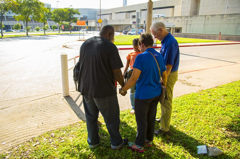 Family prays with chaplains outside Dallas' convention center