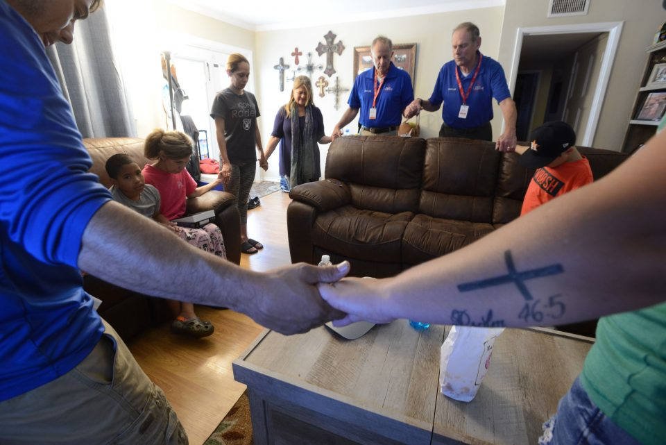 Chaplains hold hands and pray with family members