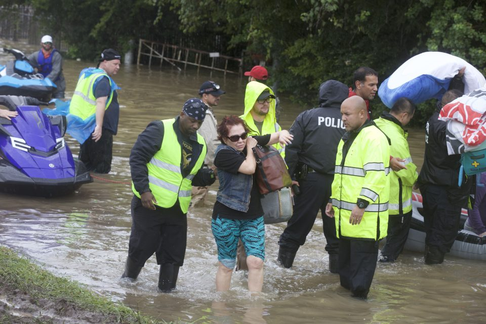 People being helped out of boat and through floodwaters