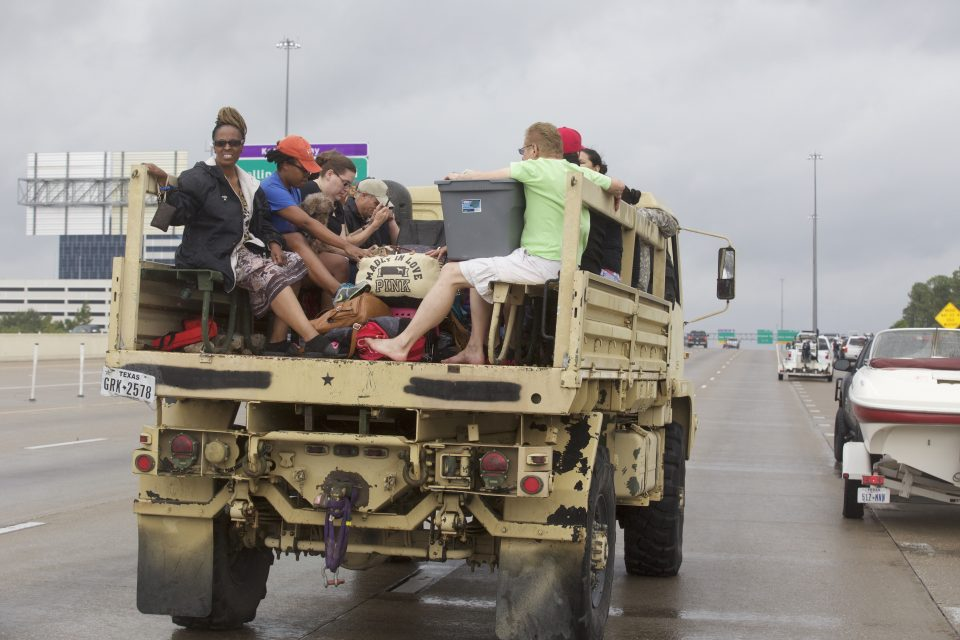 Military vehicle driving down street with evacuees on the open-air back