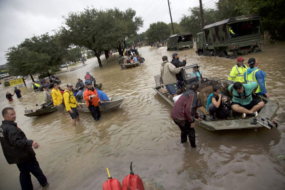 People in boats on flooded streets; rescuers