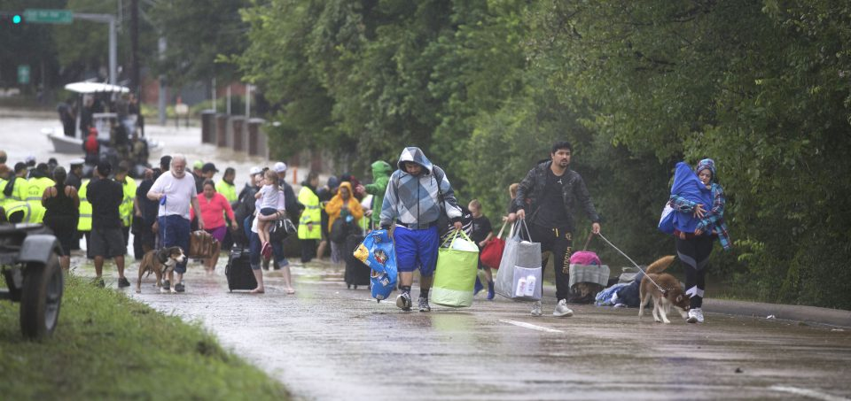 People carrying their belongings from boats to higher ground
