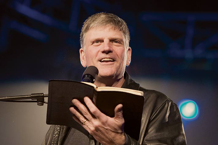 Franklin Graham preaching and holding Bible