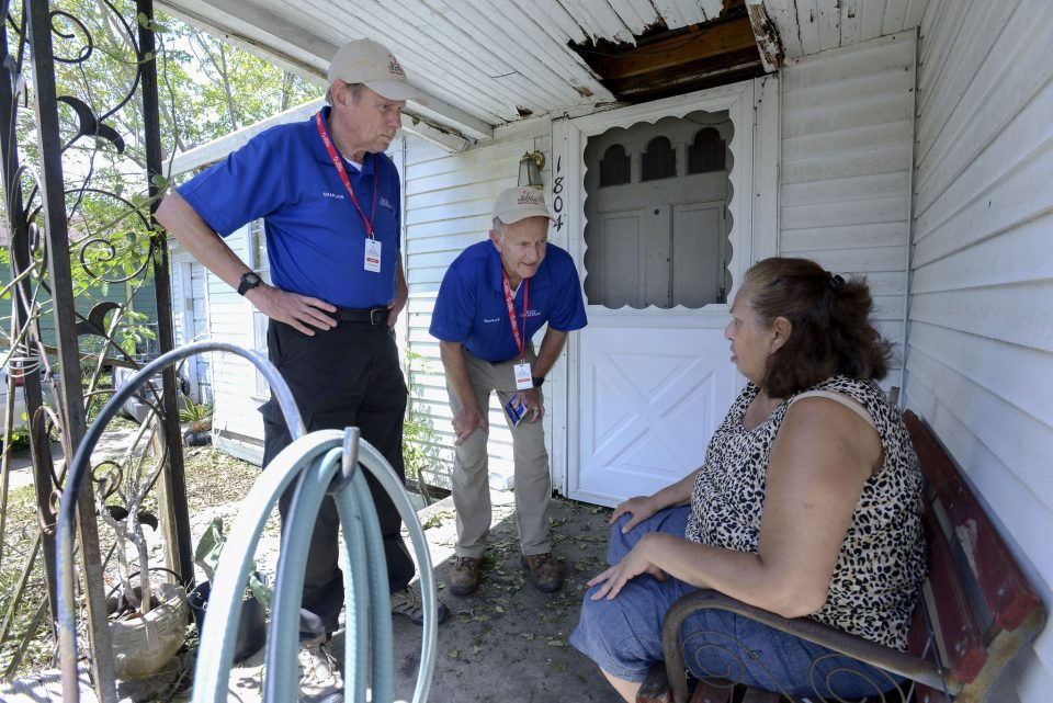 Woman sitting on porch as two chaplains listen