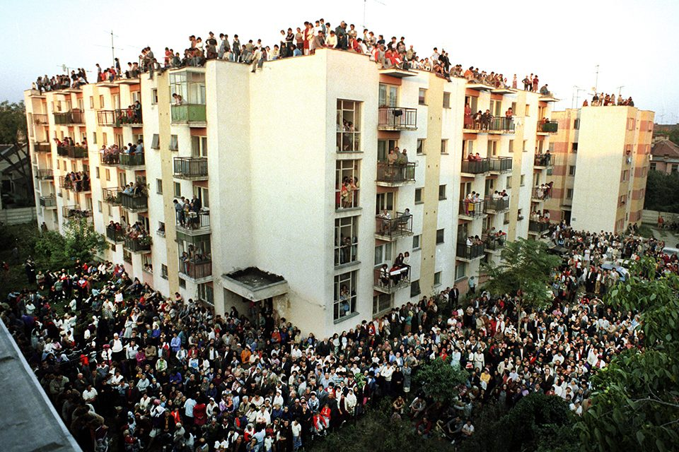 Crowds of people in the street, on balconies and the rooftop of an apartment building.