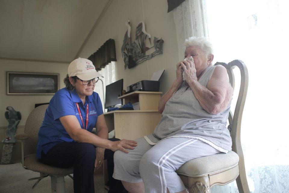 Female chaplain comforting a Naples resident who is crying
