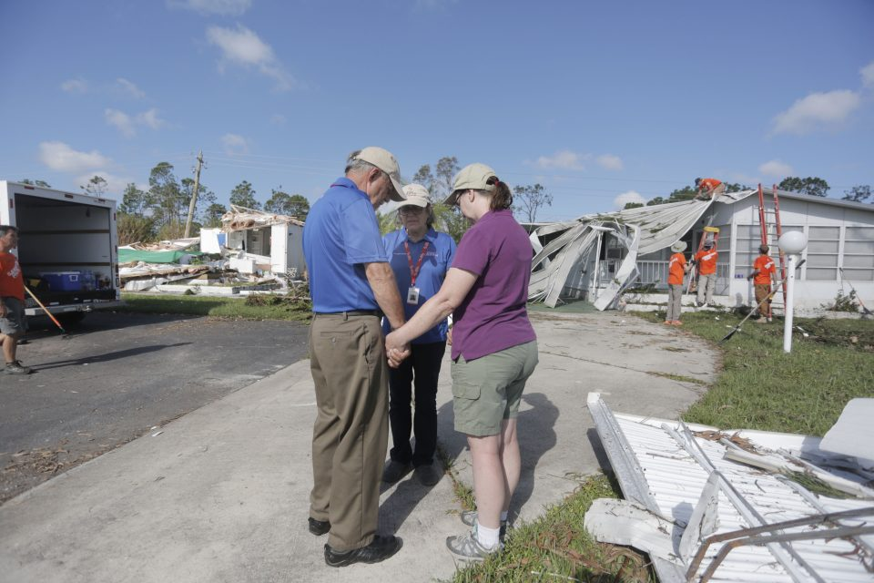 Chaplains pray with a Naples resident. In the background are heavily damage homes