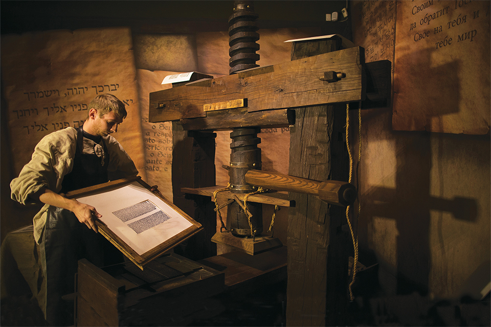 Bible Lands Museum employee in Jerusalem, Israel, standing in front of a Gutenberg replica printing press