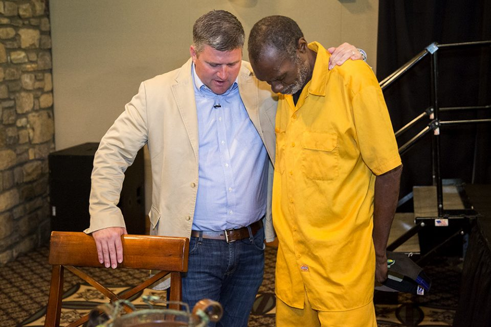 Roy Graham prays with an attendee.