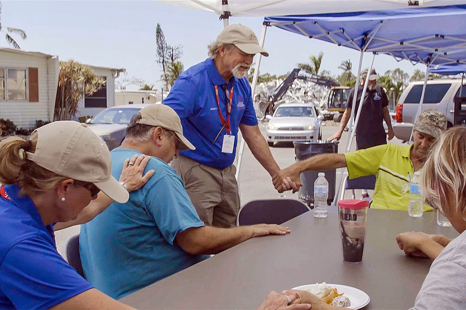 Rapid Response Team chaplains Carl and Mary Jo Hill pray with hurricane victims in Naples, Florida