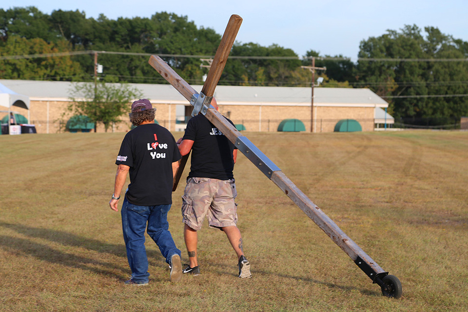 Man carrying cross and a man walking beside him
