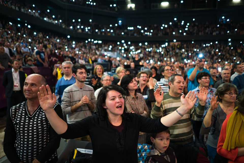 Crowd worshiping with phone flashlights in background