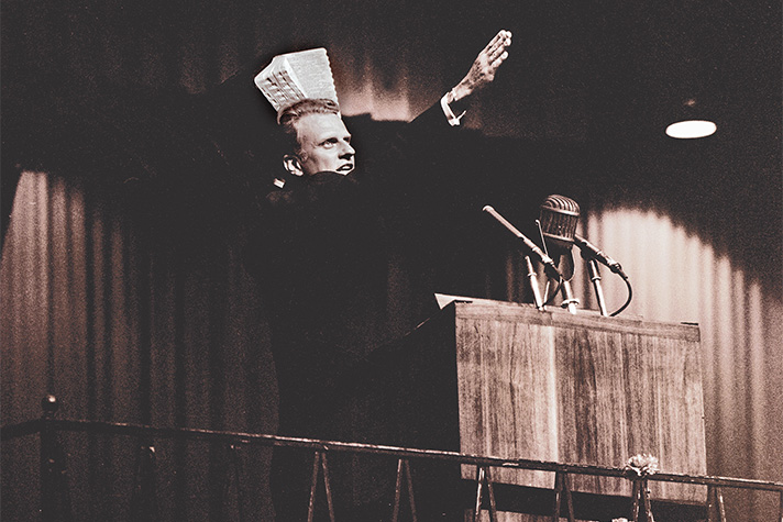 Billy Graham preaching, holding Bible