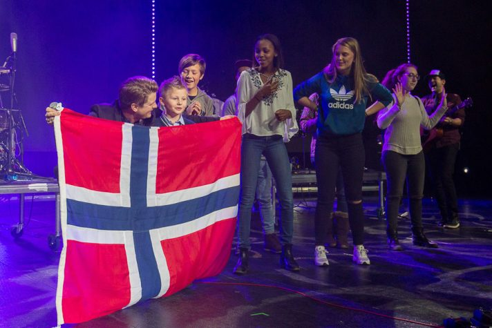 Josh Havens holding Norwegian flag in front of young boy, youth behind them