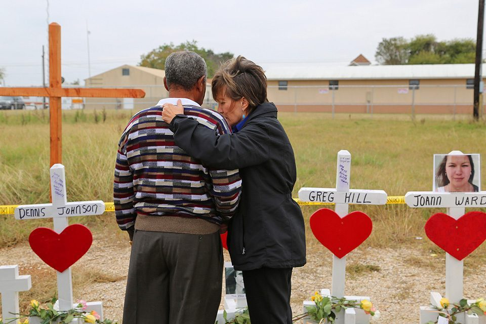 Chaplain praying with man in front of crosses representing shooting victims