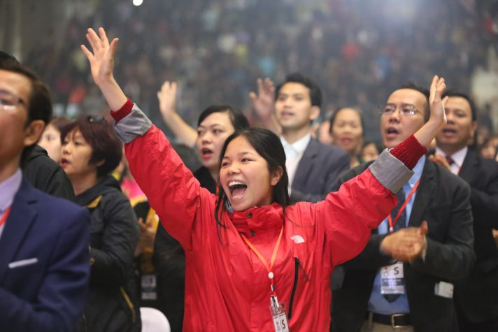Woman in red jacket, raising hands, singing in the middle of the crowd