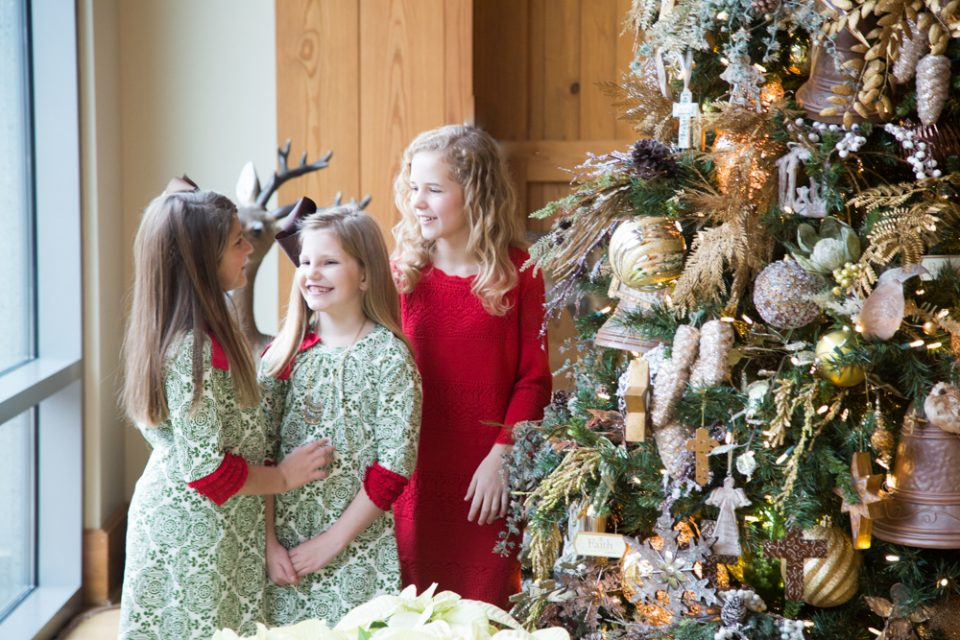 Three girls smile around the Christmas tree