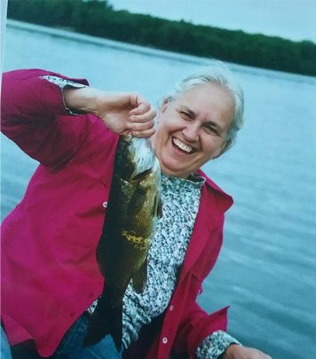 Susan Hoffman in boat holding a bass