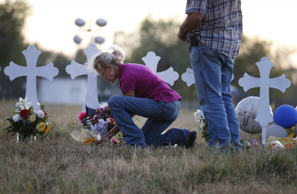 Woman lays flowers at row of crosses