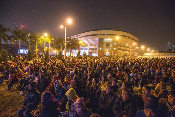 A sea of people sitting outside at night