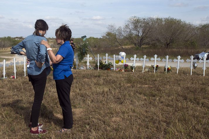 Chaplain praying with woman in front of white crosses in Sutherland Springs, Texas