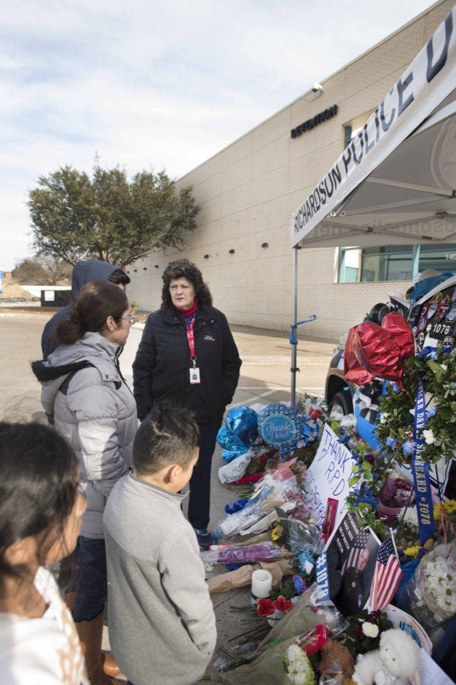 Chaplains talk to a family at a memorial site for fallen police officer David Sherrard in Richardson, Texas