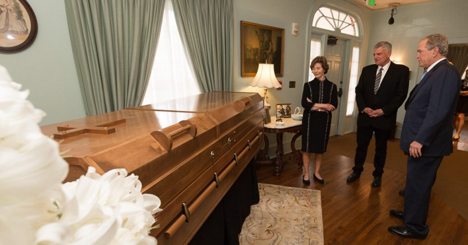 Laura Bush stands by the casket