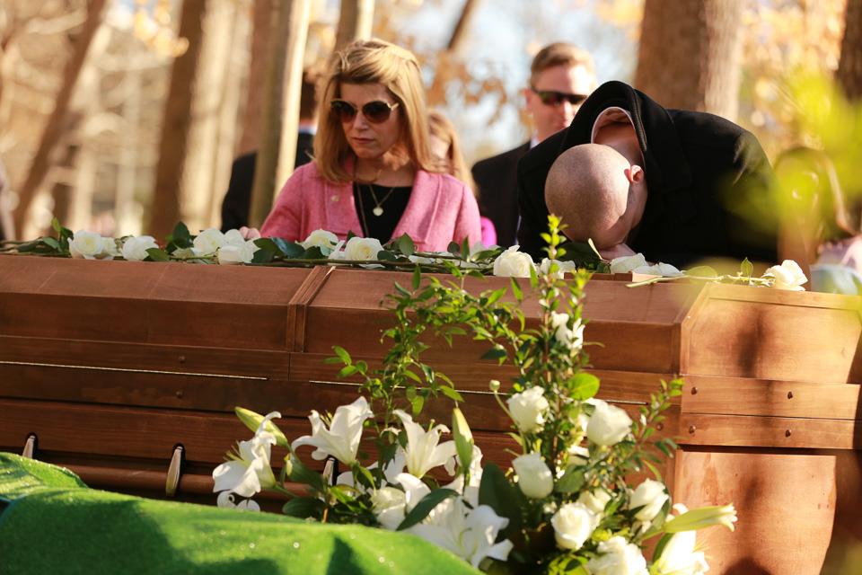 Woman and man with his head bowed on Mr. Graham's casket
