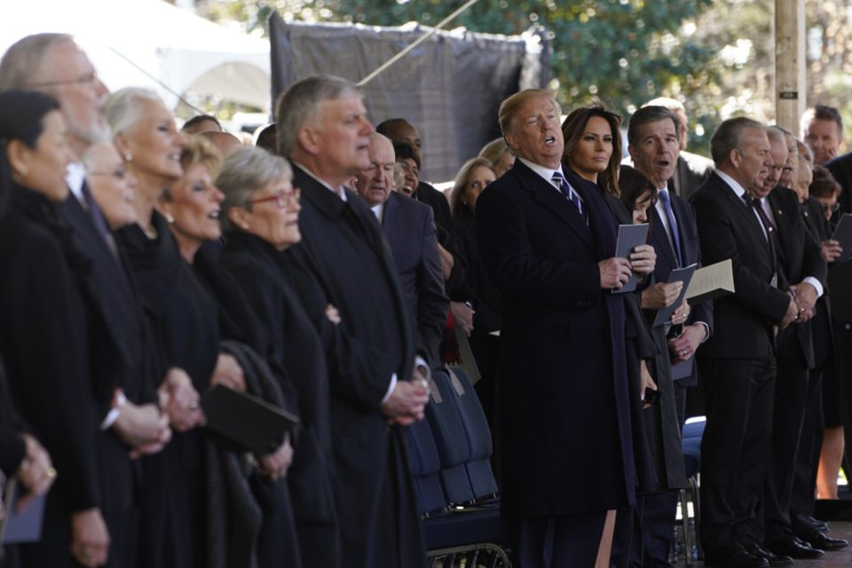 President Donald Trump listens at the funeral