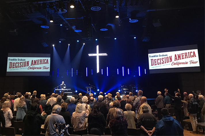 People worshiping inside church; Decision America California signs