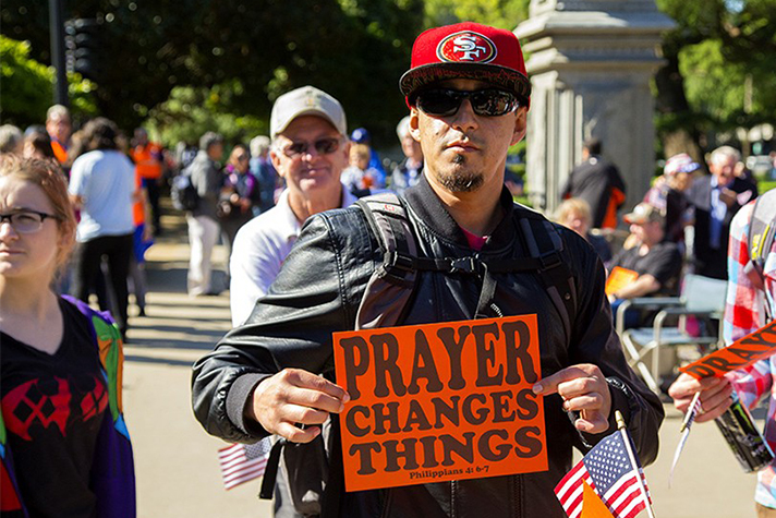 """Man holds sign that says, """"Prayer Changes Things"""""""