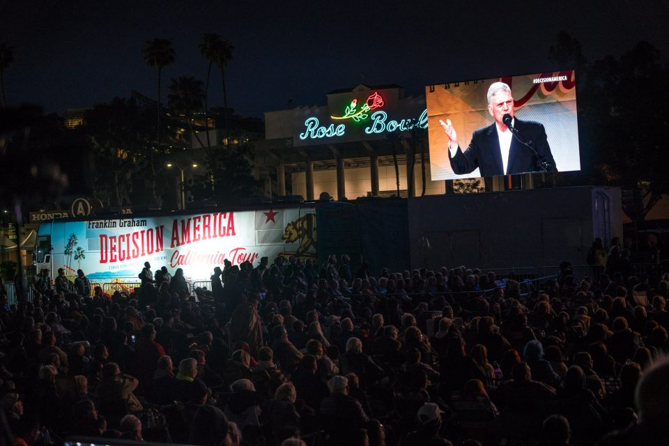 Franklin Graham on big screen with Decision California bus and Rose Bowl stadium in background
