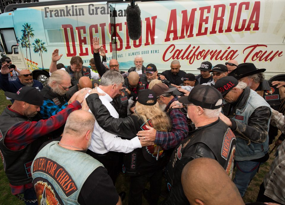 Franklin Graham praying with bikers
