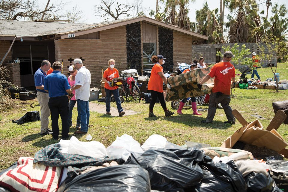 Billy Graham Rapid Response Team chaplains praying with homeowners; Samaritan's Purse volunteers moving furniture from home