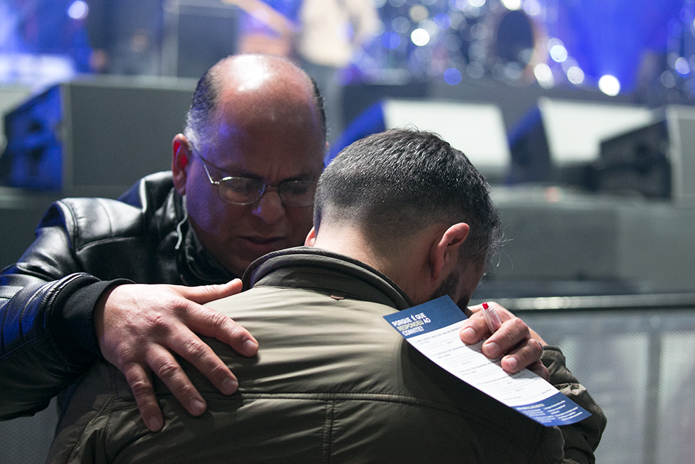man praying with young man